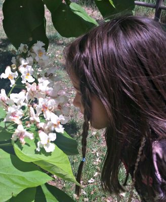 skyla smelling flowers